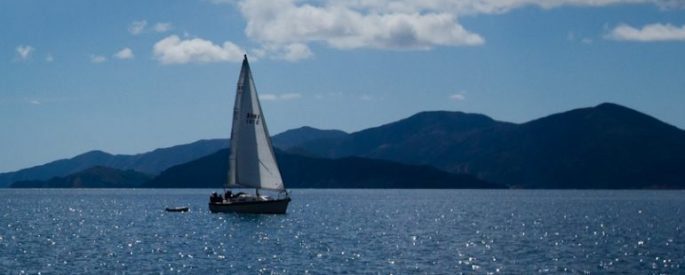 sailboat on blue waters with clouds and dark blue mountains in the background