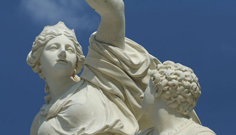 white statue of Ino with her son looking up at her, against a blue sky