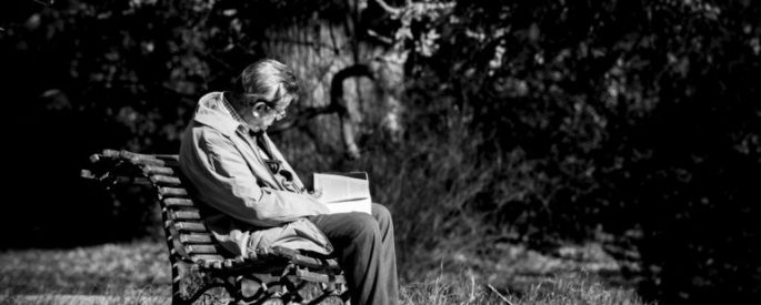 black and white photograph of old man sitting on park bench reading