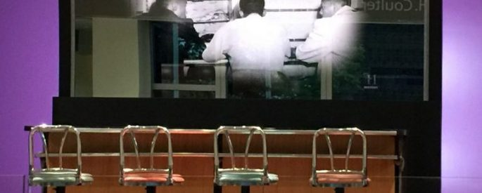 four chairs at a counter in front of a black and white photograph of the Greensboro Four