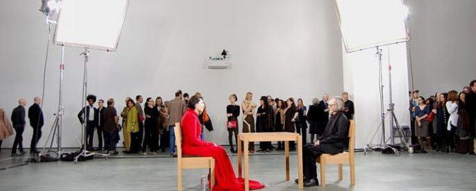 Marina Abramovic, The Artist Is Present, Marina in red sits in one chair, a guest sits in a chair across the table