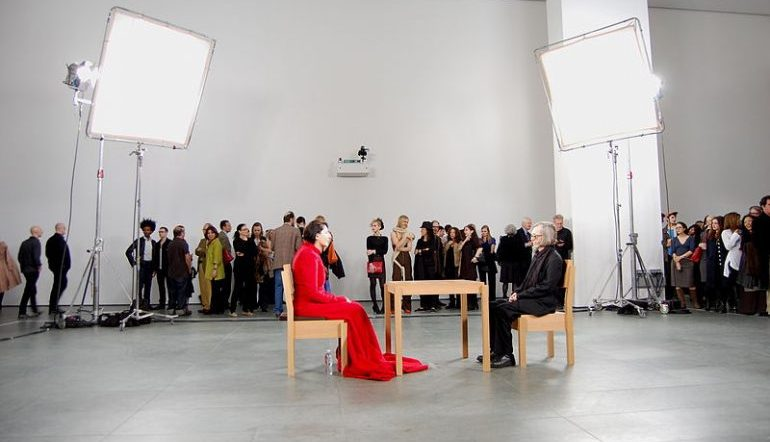 Marina Abramovic The Artist Is Present, Marina in red sits in one chair, a guest sits in a chair across the table