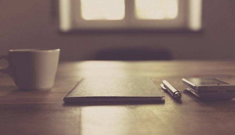 monochromatic image, a desk in front of a lit window with a cup, a notebook, a pen, and a smartphone