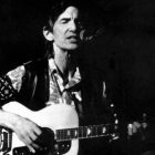 Townes Van Zandt with a guitar, singing into a microphone