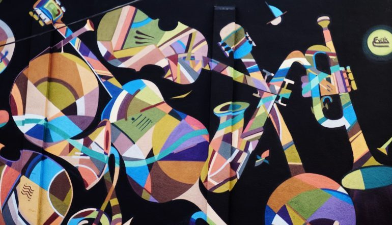 colorful, mosaic-like instruments against a black background