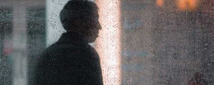 silhouette of a person through a dewy window
