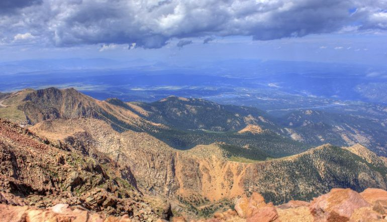 mountain view of the Rockies and the landscape beyond, dark clouds hover in the sky