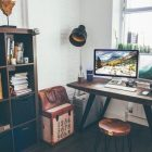 study room with bookcase, lamp, desk, computer monitors, stool