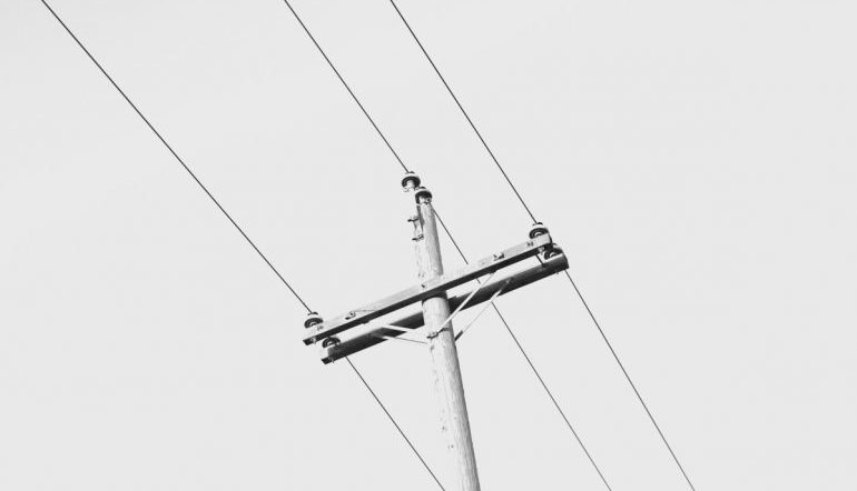 view from the ground of a telephone pole with wires
