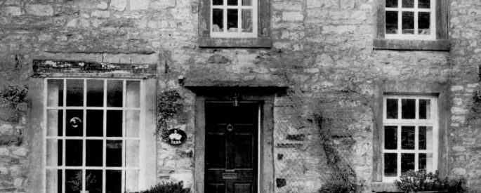 black and white photograph of the front of a cottage - door, windows, stone wall
