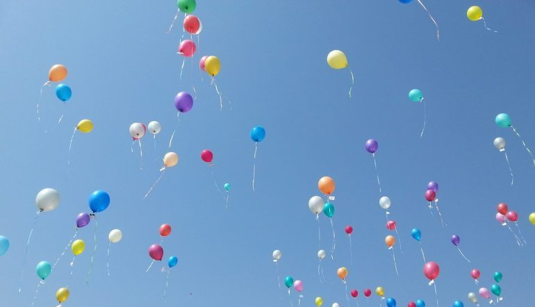 airborne balloons of various colors against a blue sky