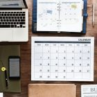 desktop with laptop, calendar, planner, clock