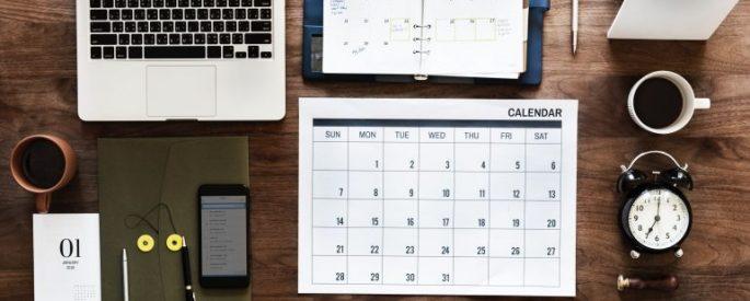 desktop with laptop, calendar, planner, clock