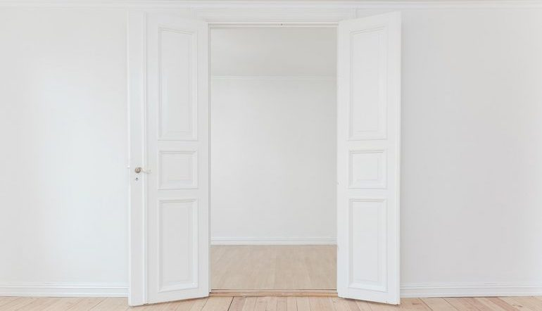 open white double-door with while walls and light wood floor