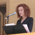 woman speaking at a stand with a microphone