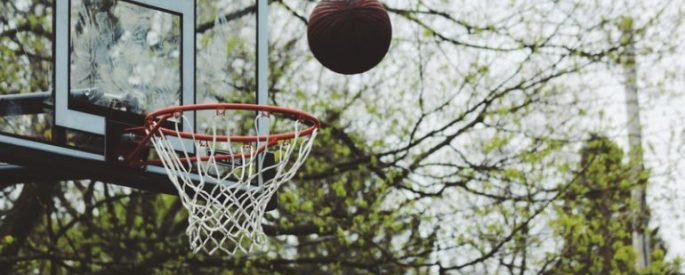a basketball arcing into the net