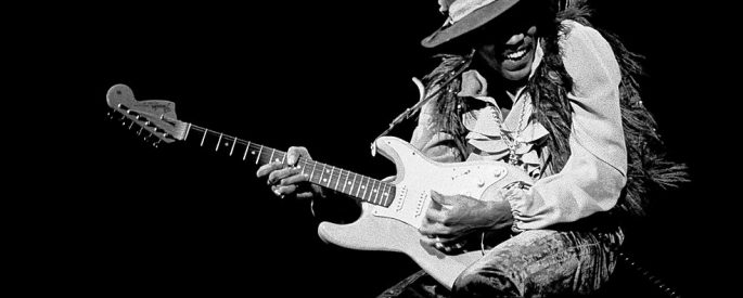 Black and white photo of Jimi Hendrix playing the guitar on stage.