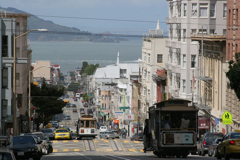 Photograph of the view from the top of Nob Hill, showing a hilly street with streetcars