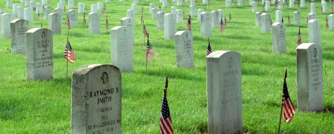 photograph of a graveyard that stretches into the horizon of the photograph on a grassy hill - the graves all have US flags placed at them