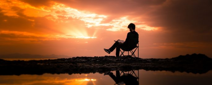 Image of a man sitting, reading a book outside during a sunset