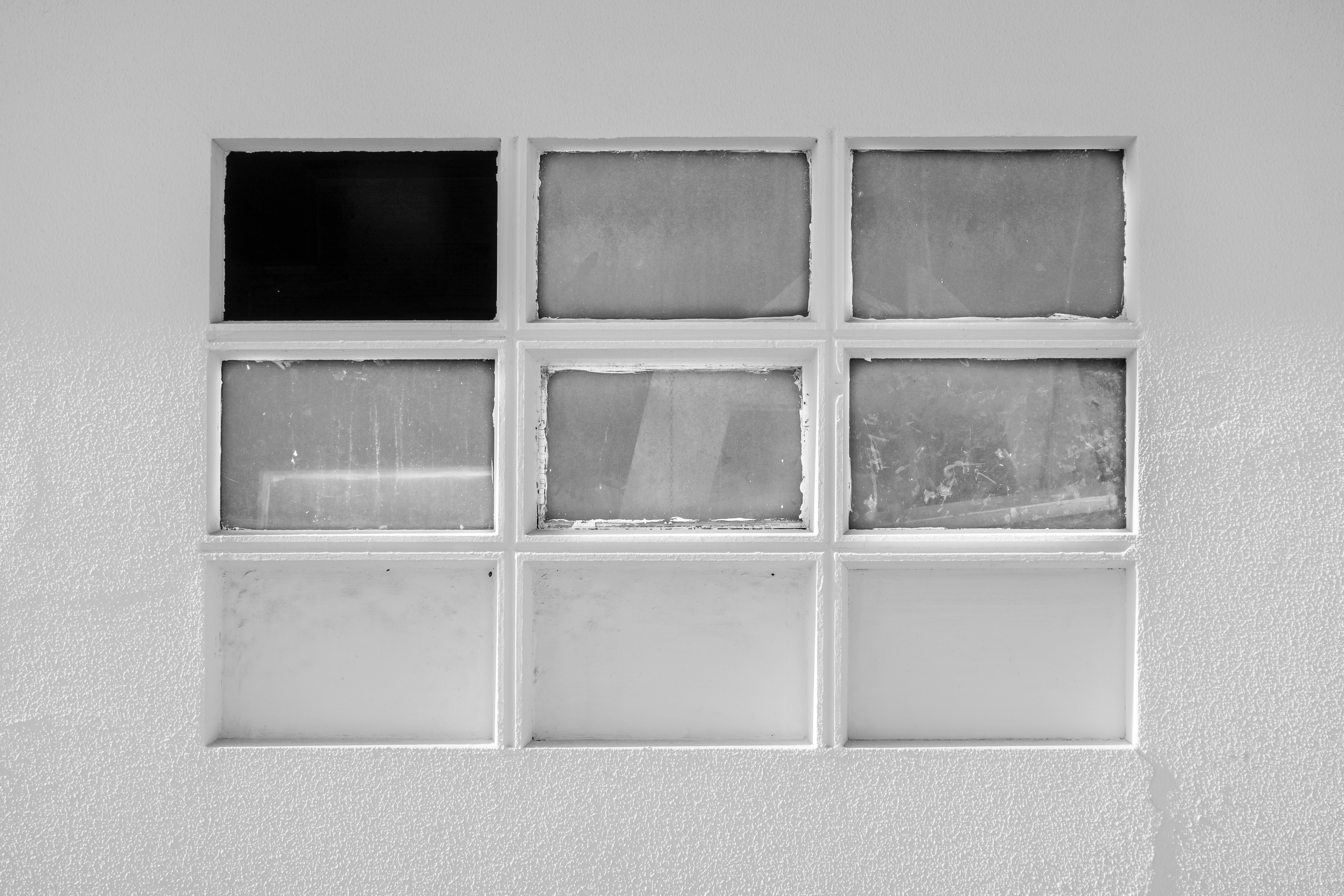 Black and white image of a window with a missing pane.