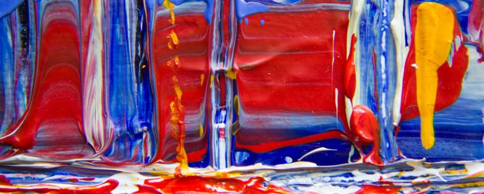 A photograph of an abstract painting with lots of reds and blues.