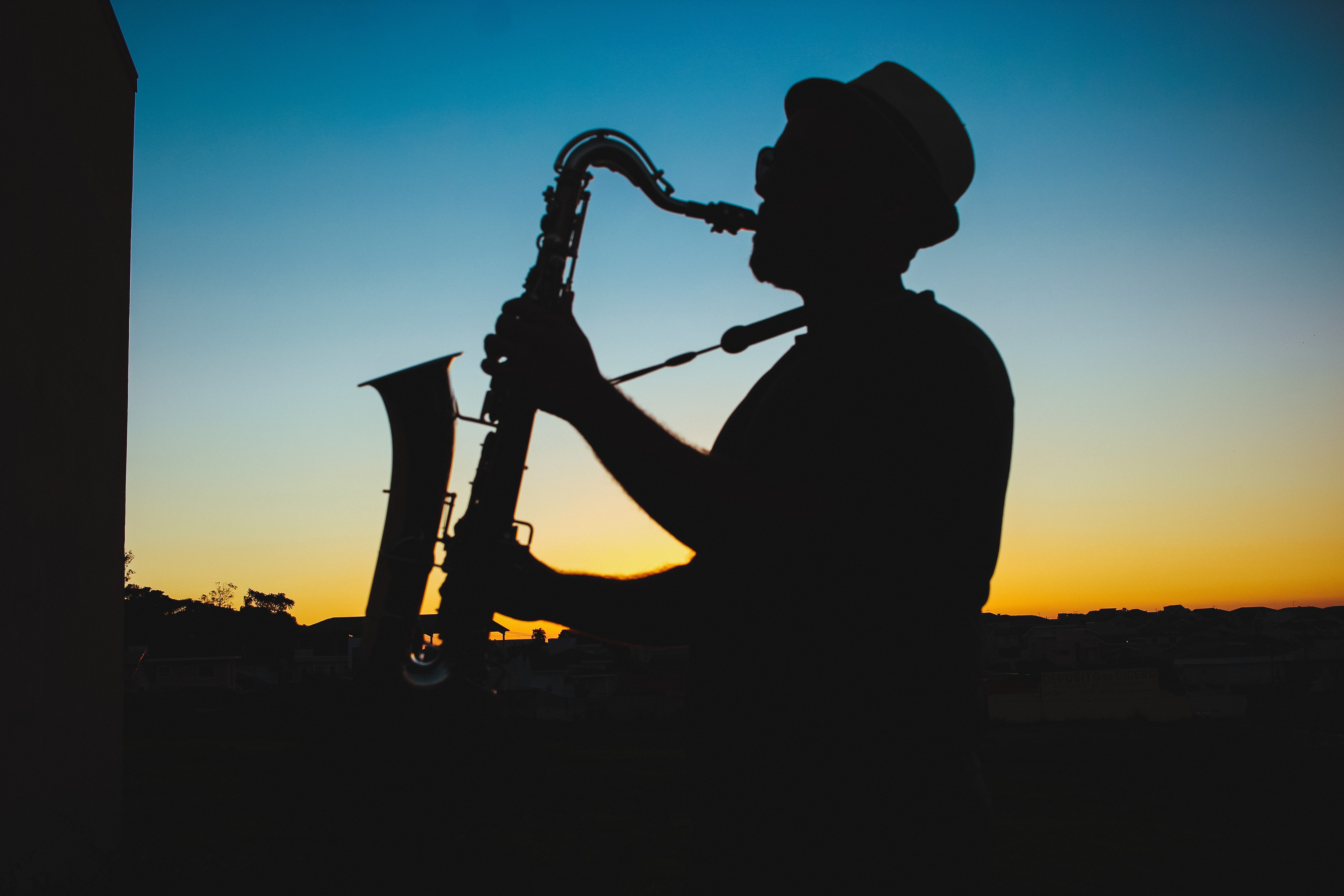 Photograph of a saxophone player silhouetted against a blue and orange sky
