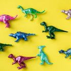 Bright colored dinosaur toys played out against a bright yellow background.