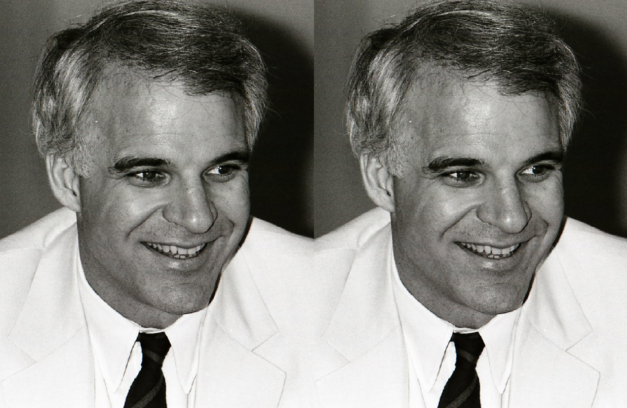 Black and white photograph of Steve Martin smiling in a suit and tie