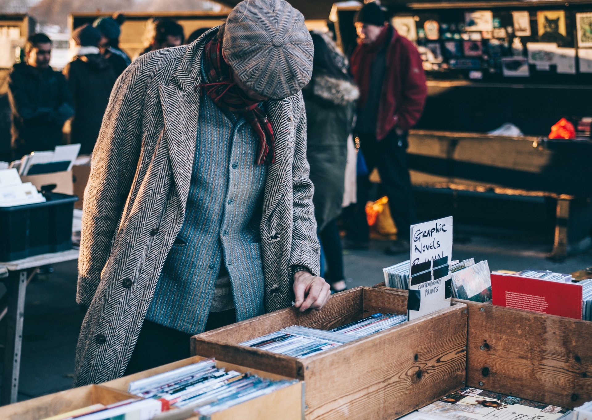 Photograph of a man browsing books in an outdoor market