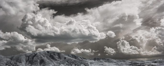Black and white photograph of storm clouds over a snow-covered mountain range