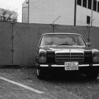 Black and white photograph of an old car in front of a cement wall with barbed wire