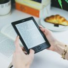 Photograph if a person's hands holding a Kindle with a table in the background