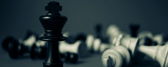 Photograph of a black chess piece standing among tipped over white pieces