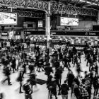 Black and white, blurred photograph of a crowd in a large train station