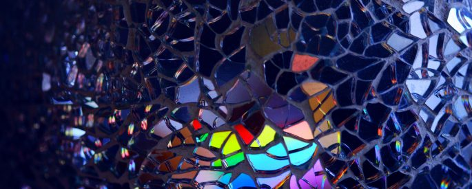 Image of glass fragments reflecting rainbow patterns