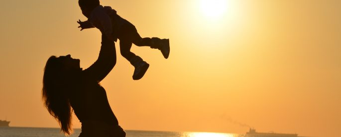 Photograph of the silhouette of a mother holding her child at the beach