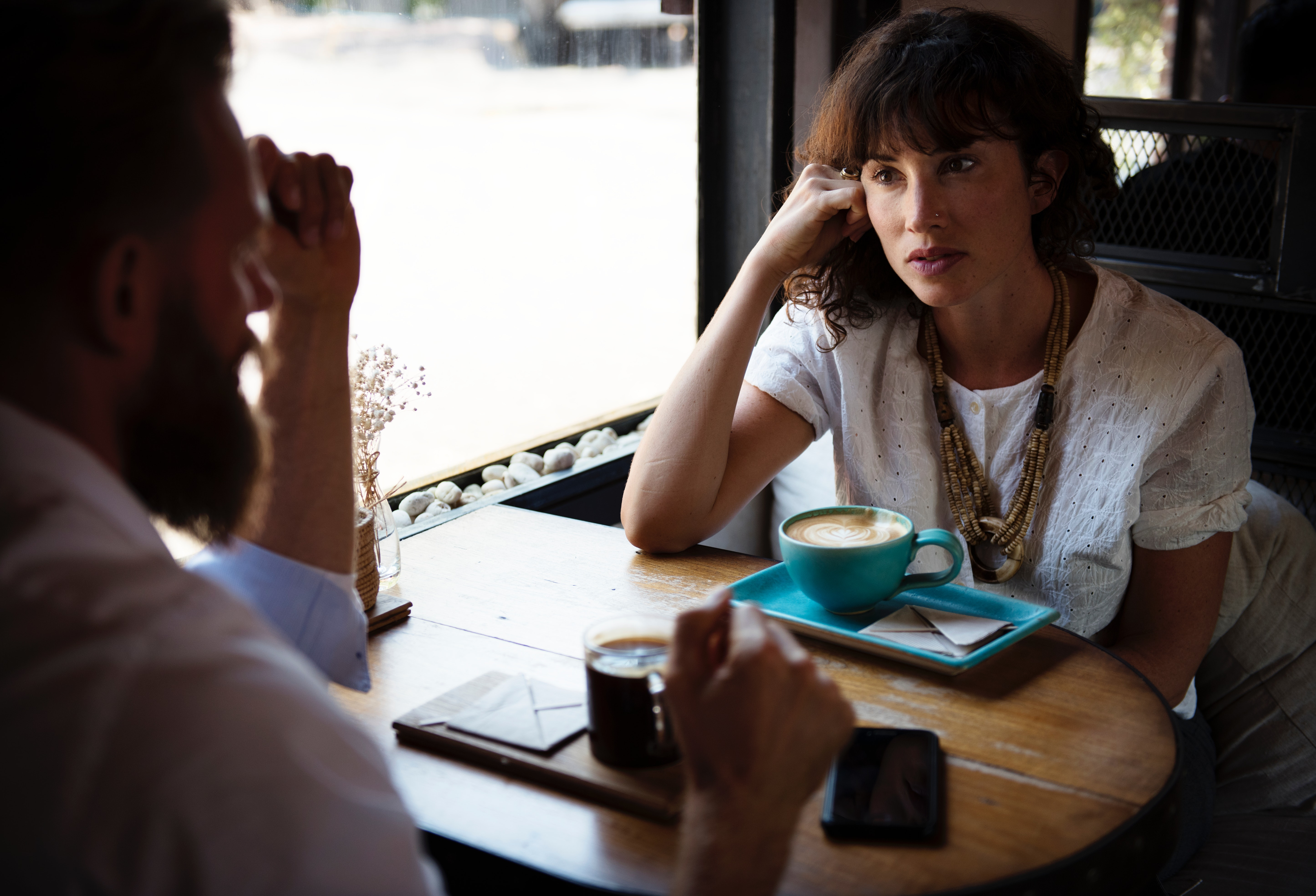 Photograph of a man and a woman having a conversation over a cup of coffee at a cafe