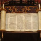 Photograph of an old Torah scroll open and resting on a wooden table
