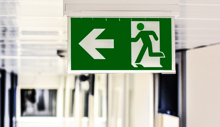 green exit sign above a door features a large arrow and a figure following it