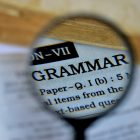 "Photograph of a magnifying glass over the dictionary definition of ""grammar"""