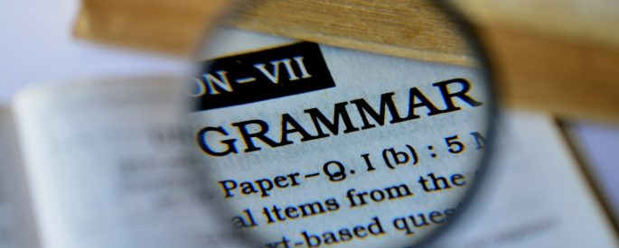 """Photograph of a magnifying glass over the dictionary definition of """"grammar"""""""