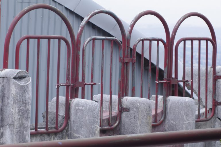 image shows a series of red, rusting gates side by side