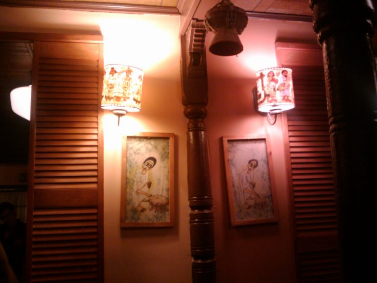 a mirrored image of a room is lit by orange and red lights, decorated with lamps and paintings and wood panels