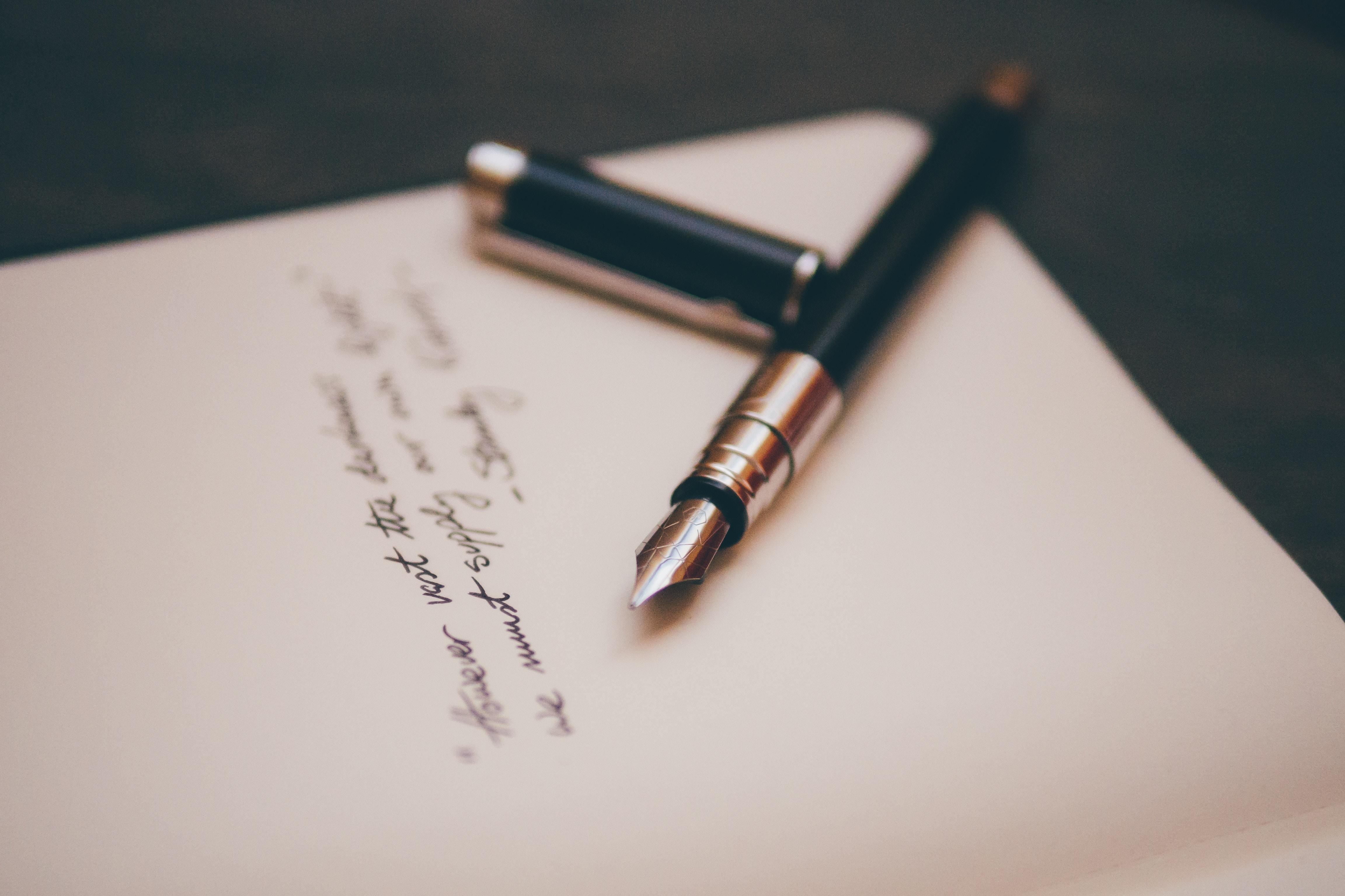 A black fountain pen sits atop a half-written letter.
