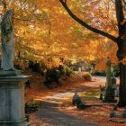 image of a tall stone statue next to a small path in a park at autumn--the surrounding trees are bright orange, covered in autumn foliage