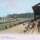 In a vintage postcard style photo, people sit in the bleachers in front of a horseracing track.