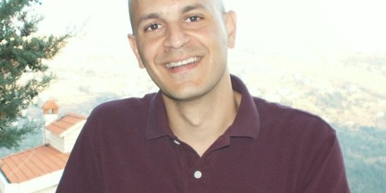 image of Fady Joudah, who poses for the portrait in a maroon golf shirt