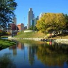image of Downtown Omaha city skyline in a bright, sunlit park with a lake