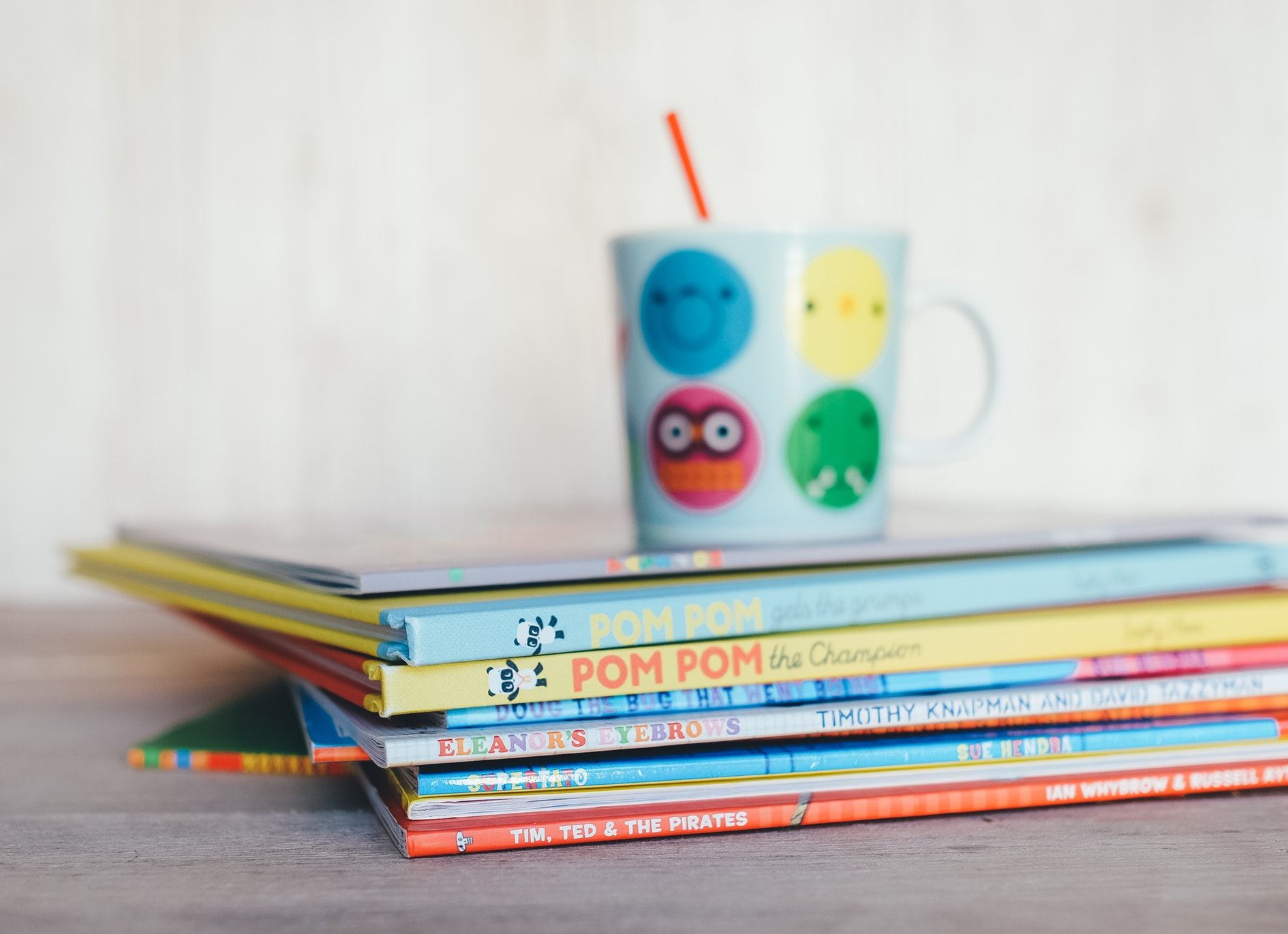 Stacked, colorful children's books sit on a table stacked on top of one another.